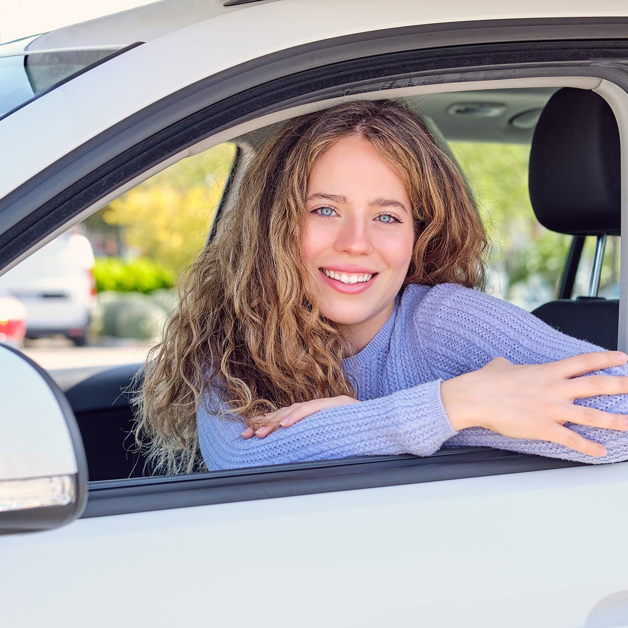 Cheerful young female driver in casual wear sitting in car parked in sunny city street and looking at camera with pretty smile